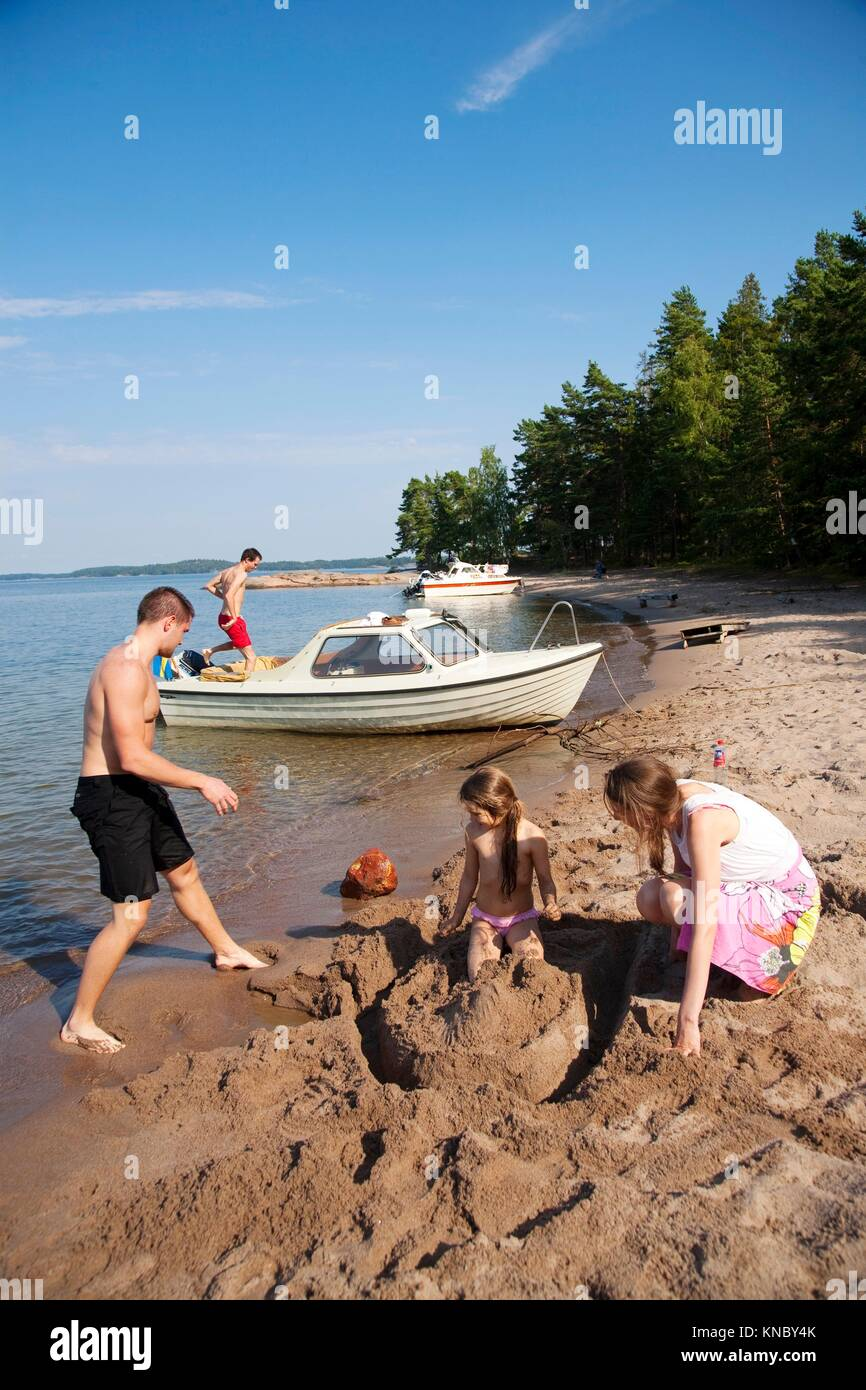 Family building sand castle, Swedish archipelago. - Stock Image