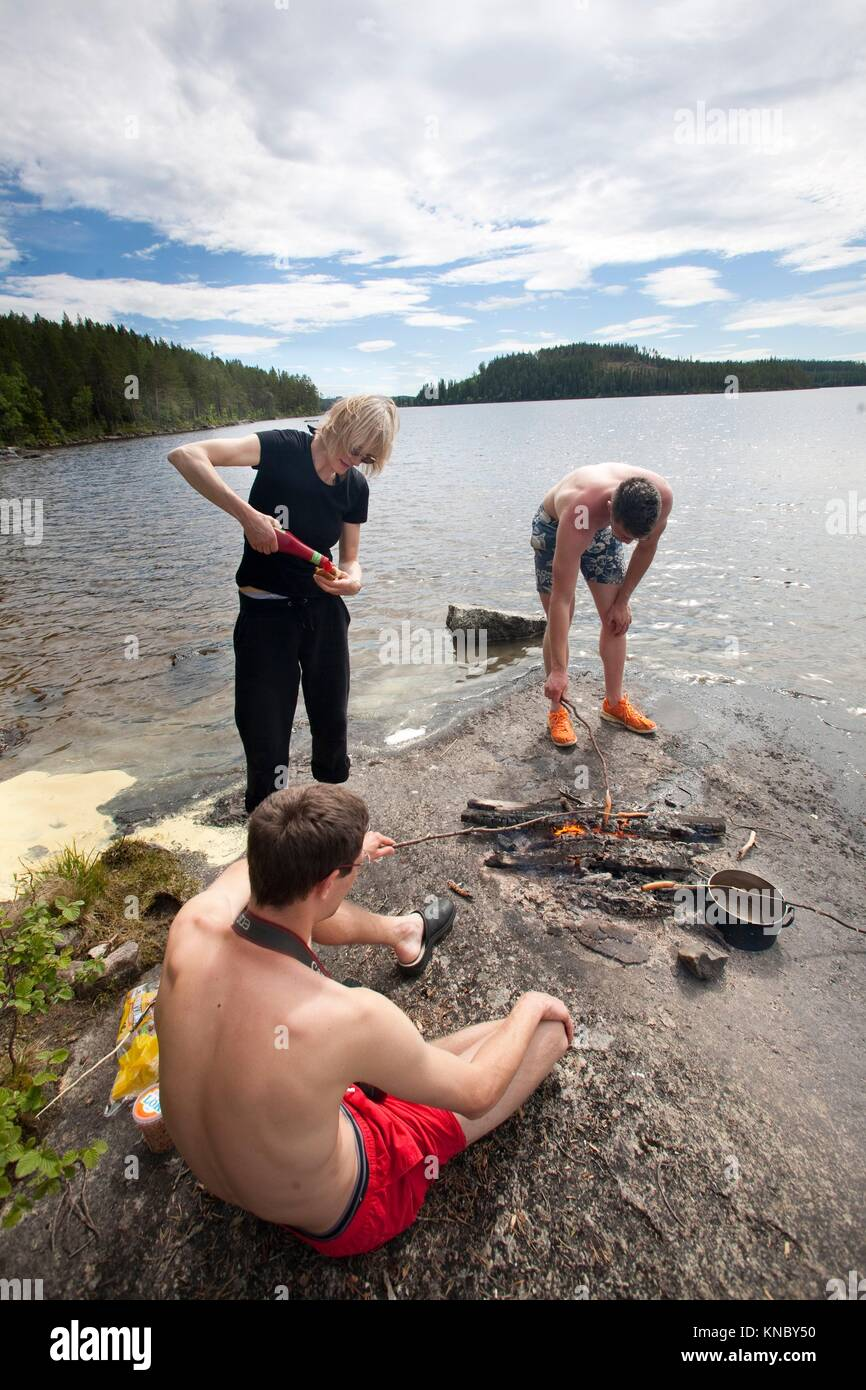 Family grilling hot dogs by the water, countryside of northern Sweden. - Stock Image