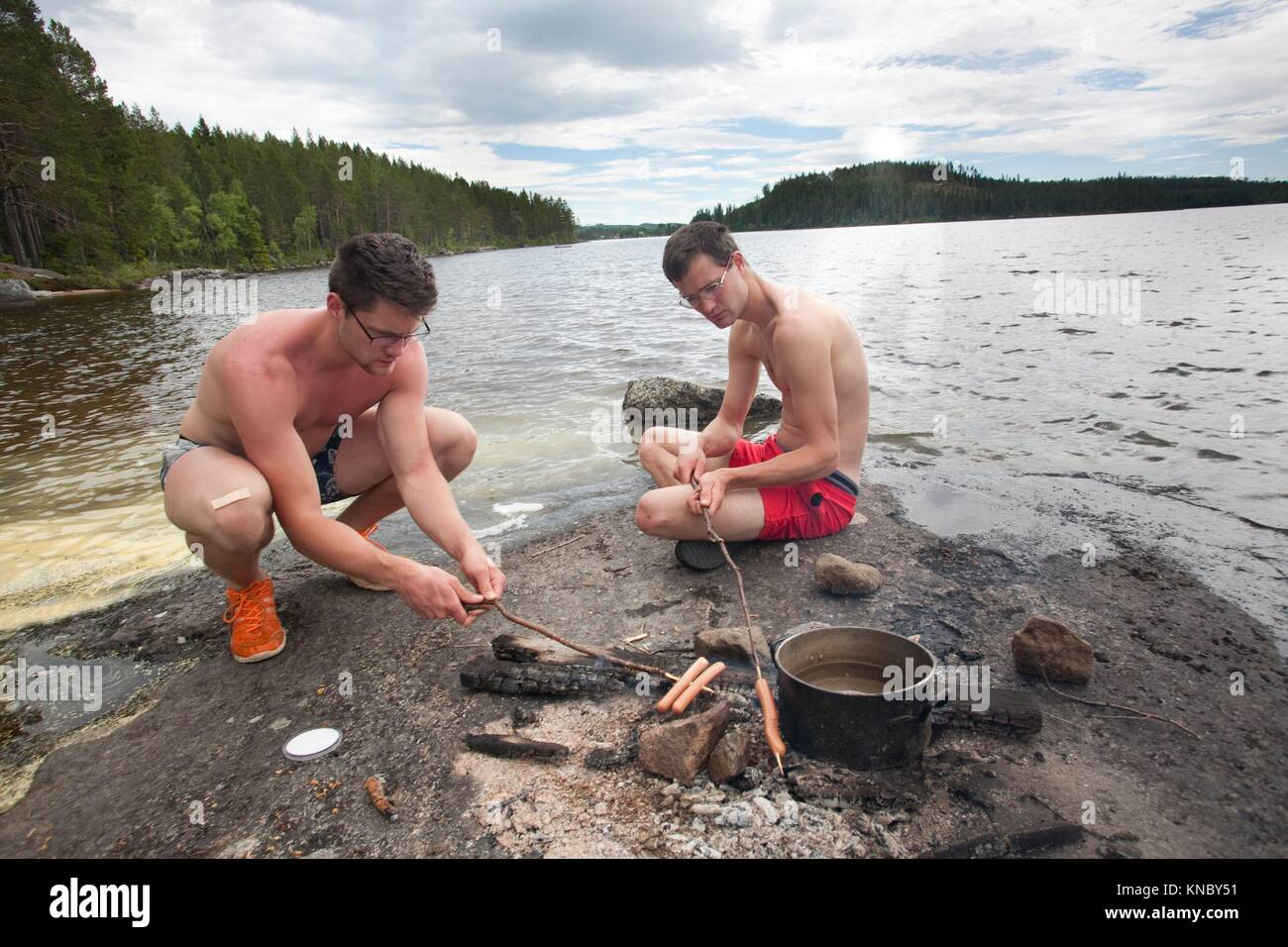 Brothers grilling hot dogs by the water, countryside of northern Sweden. - Stock Image