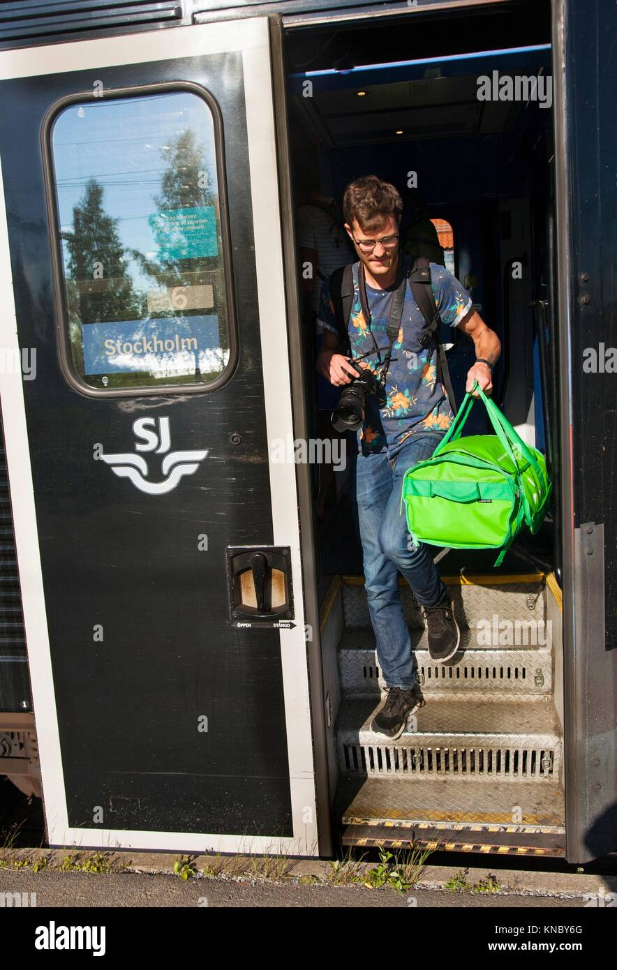 Man stepping off train Northern Sweden. - Stock Image