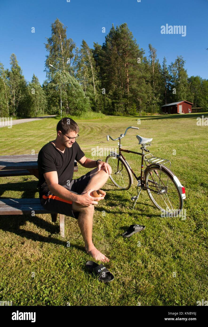 Man sitting in the sun, Northern Sweden. - Stock Image