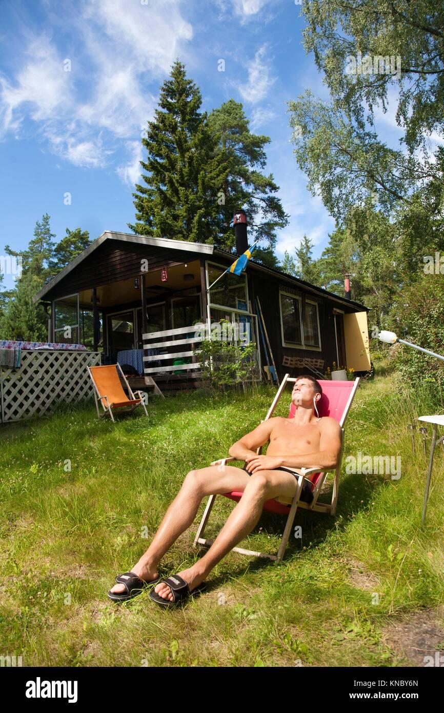 Man sunbathing, Swedish archipelago near Stockholm. - Stock Image