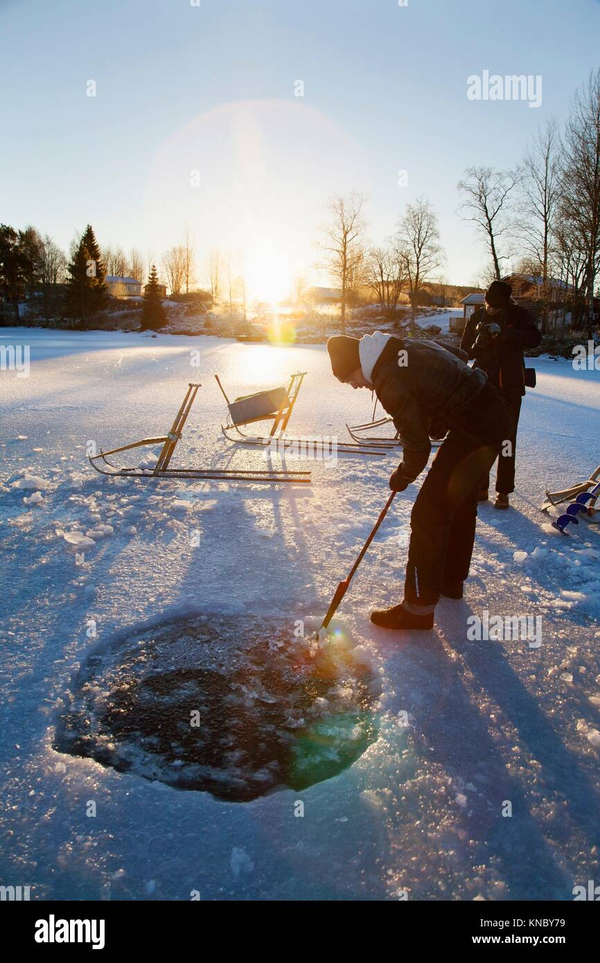 Man making a hole in the ice Northern Sweden. - Stock Image