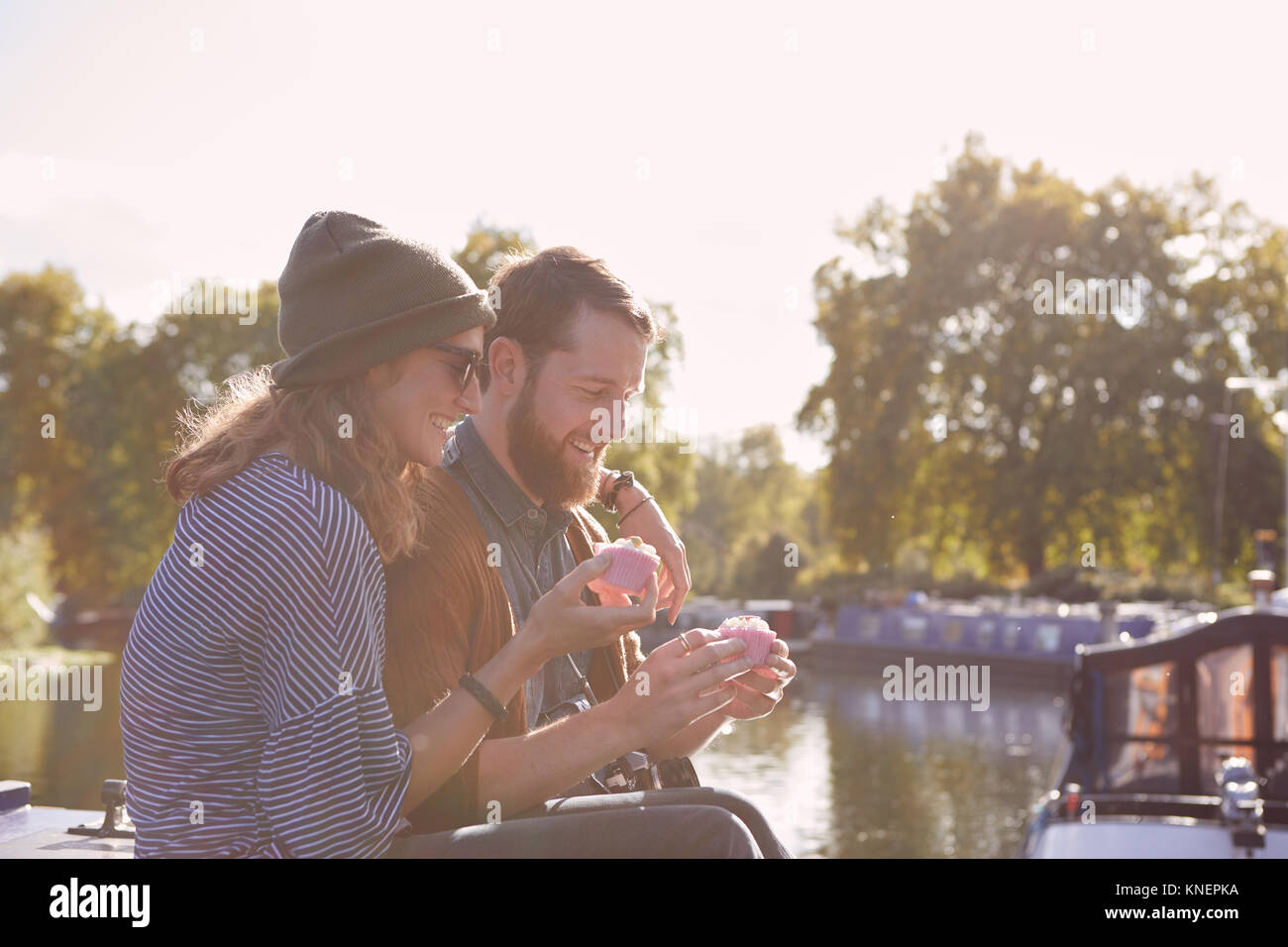 Couple eating cupcakes on canal boat - Stock Image