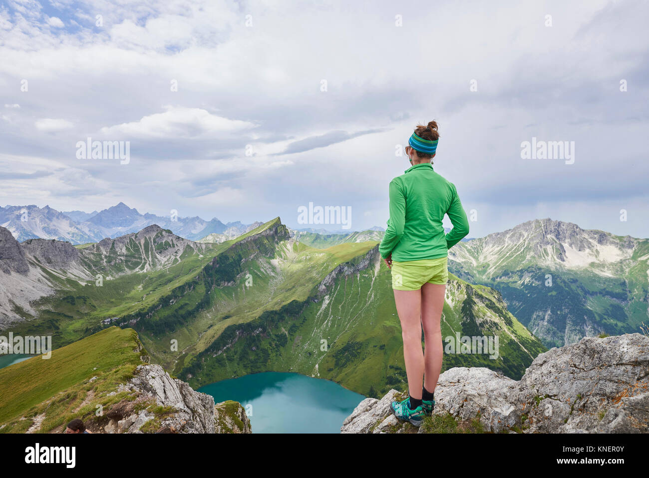 Rear view of female hiker on rocky edge looking out over Tannheim mountains, Tyrol, Austria - Stock Image