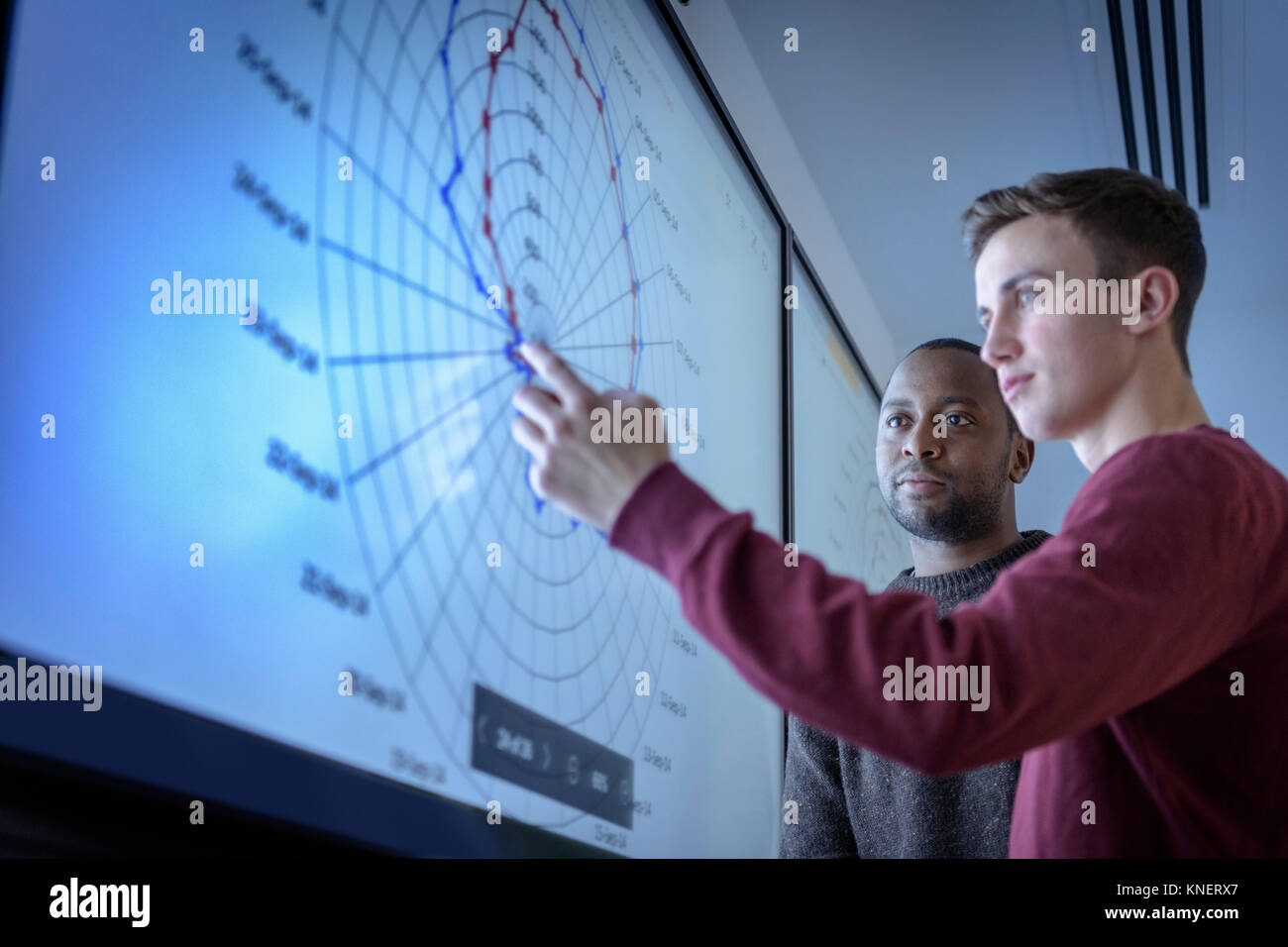 Teacher and apprentice studying graphical screen display in railway engineering facility - Stock Image