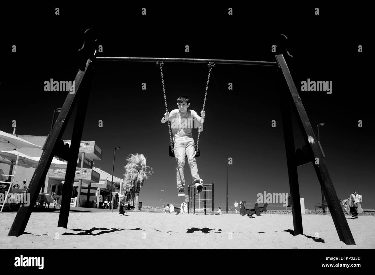 Child swinging in Castellon, Spain. - Stock Image