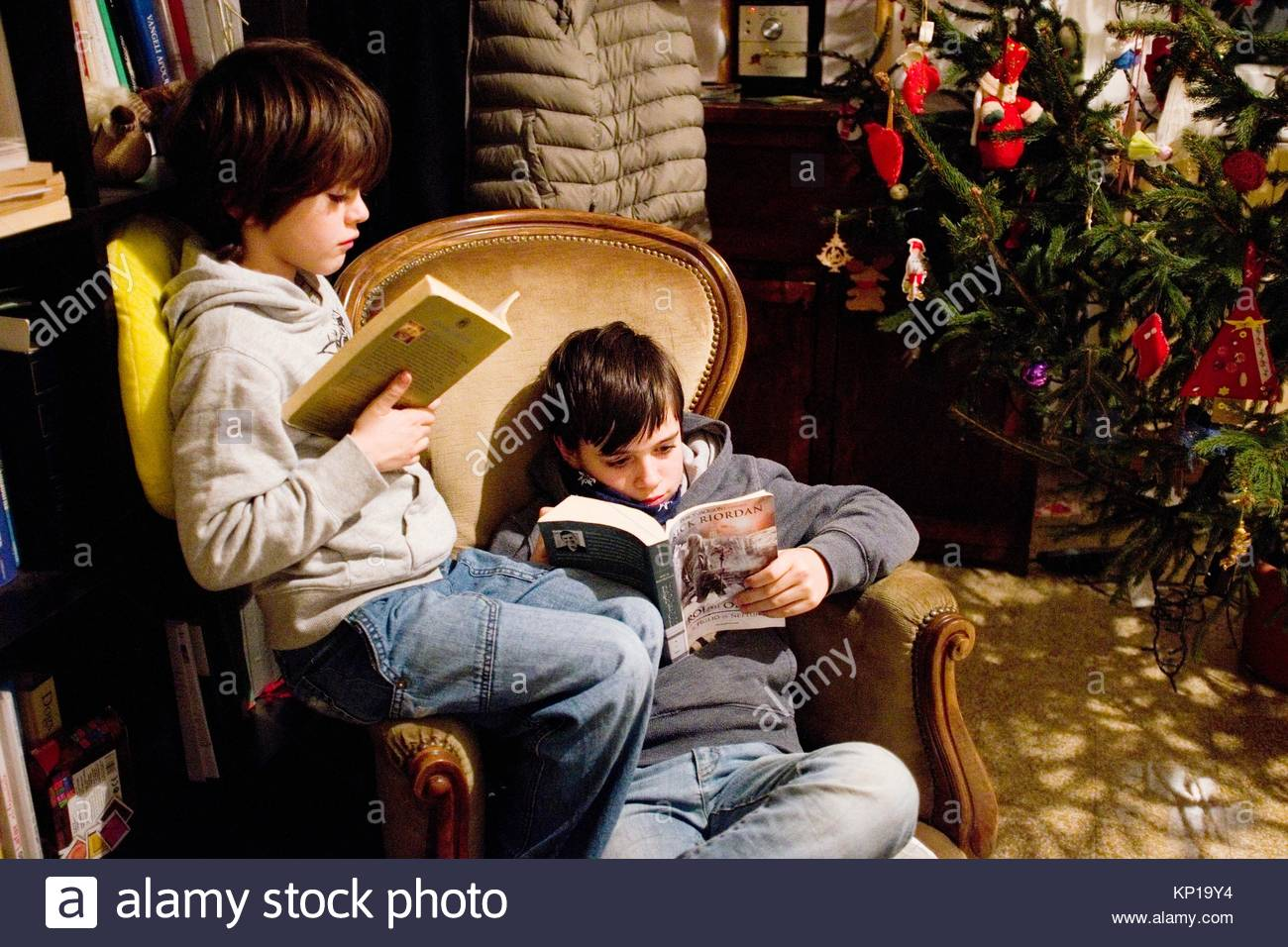 children read a book in their living room - Stock Image