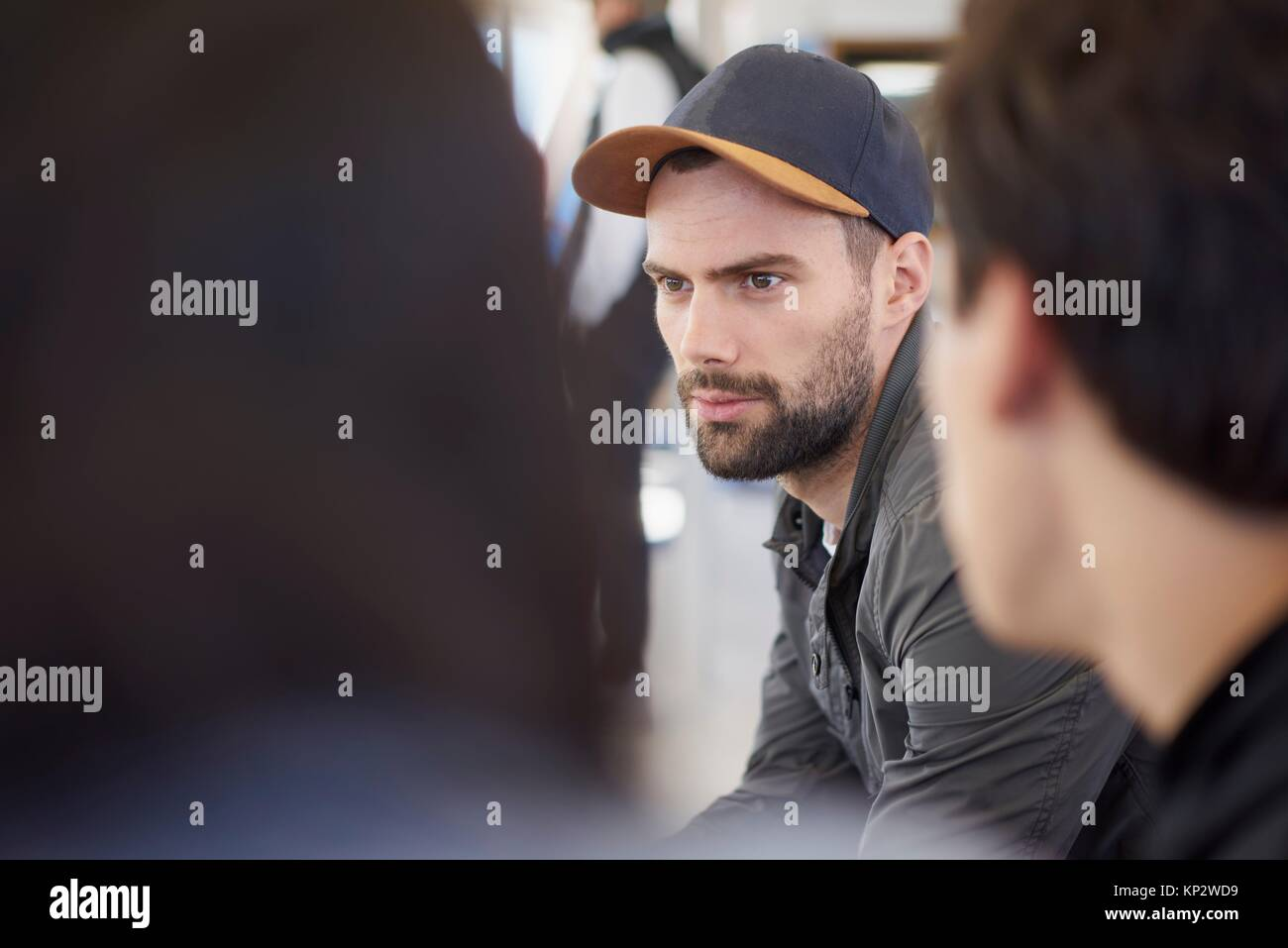 Thoughtful, distracted young man is daydreaming during conversation with friends - Stock Image