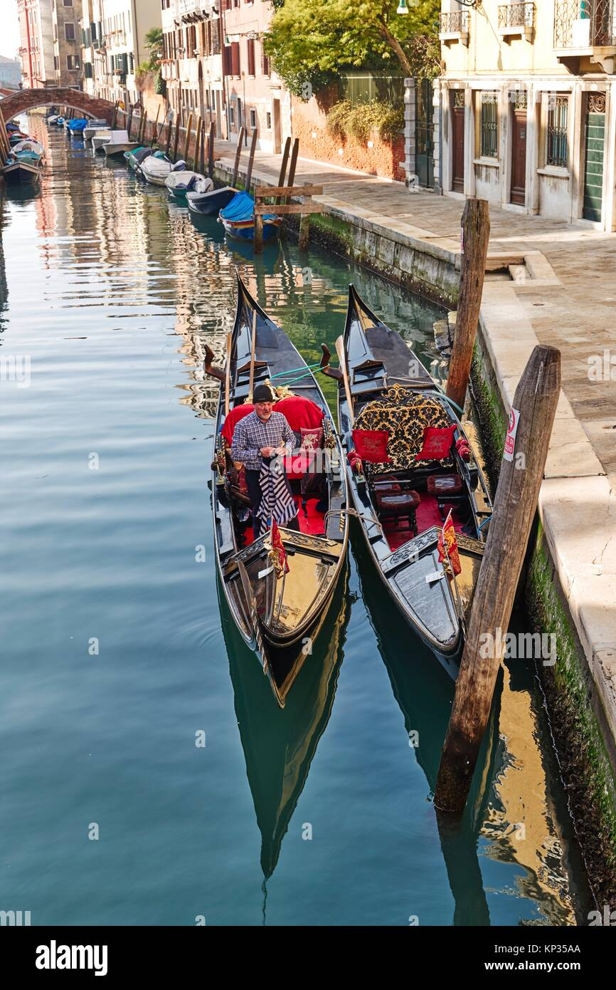 Gondolas moored in a canal in Venice, Italy - Stock Image
