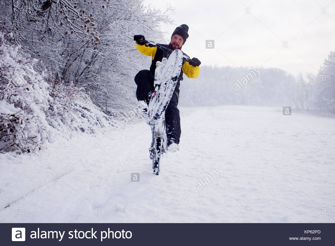 cyclist enjoys riding on snow-covered trails - Stock Image