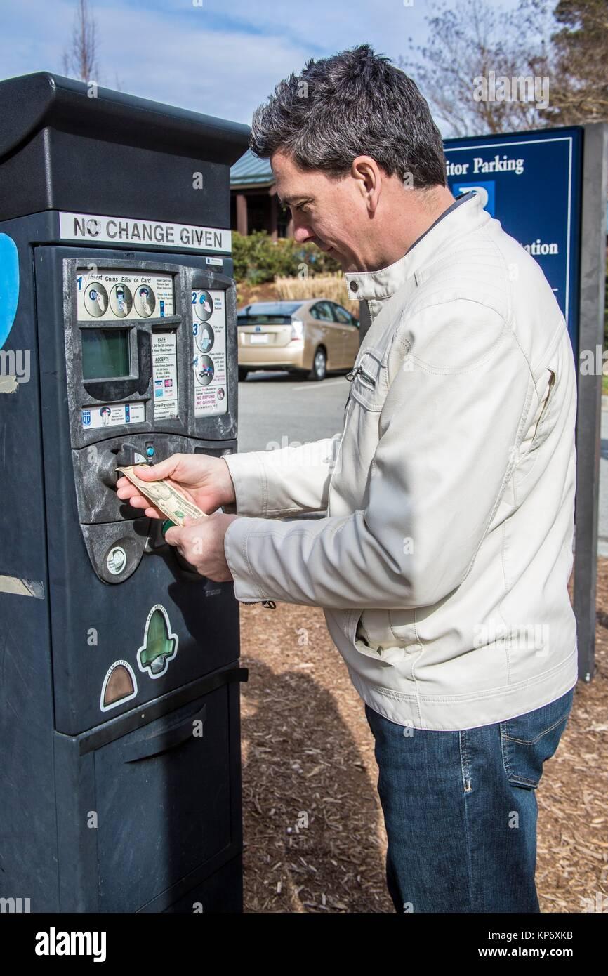 caucasian man with dark hair in his 40´s, 45´s putting cash dollar money in the car meter. - Stock Image