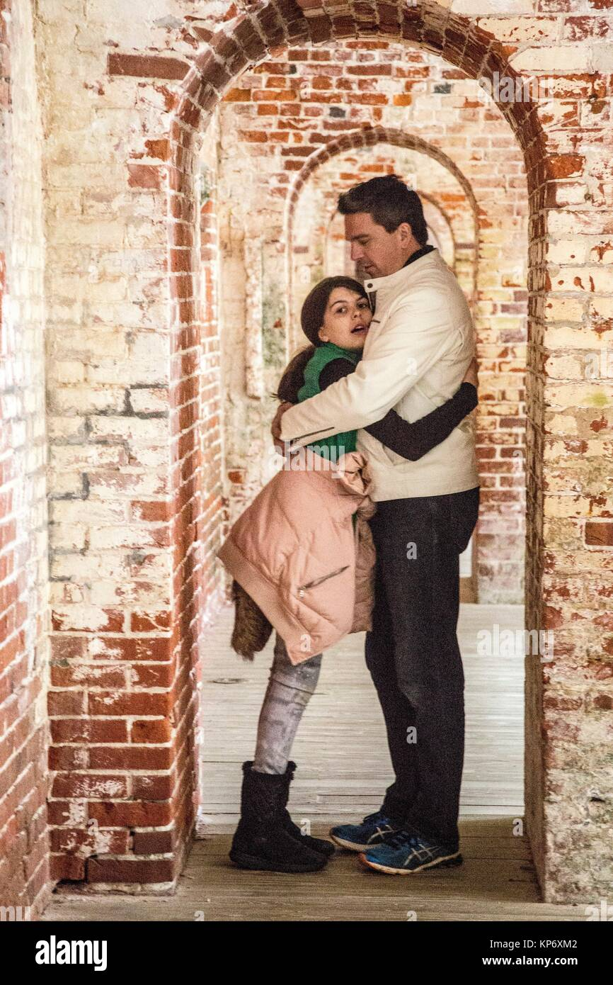 Handsome dark hair father with a white leather jacket with his preteen daughter in the between of the arched doors - Stock Image