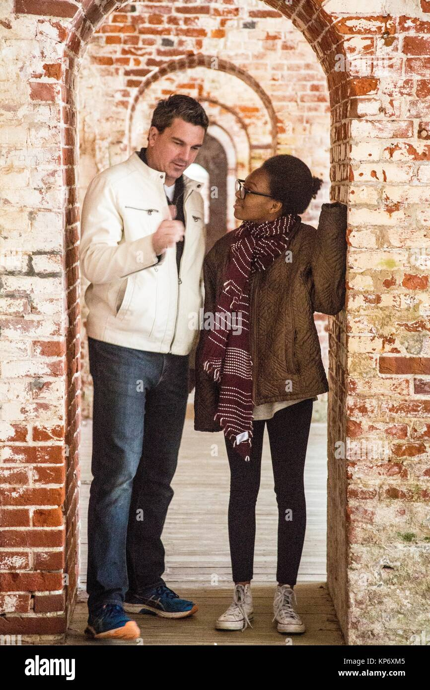 Handsome dark hair father with a white leather jacket with his adopted african american teen daughter in the between - Stock Image