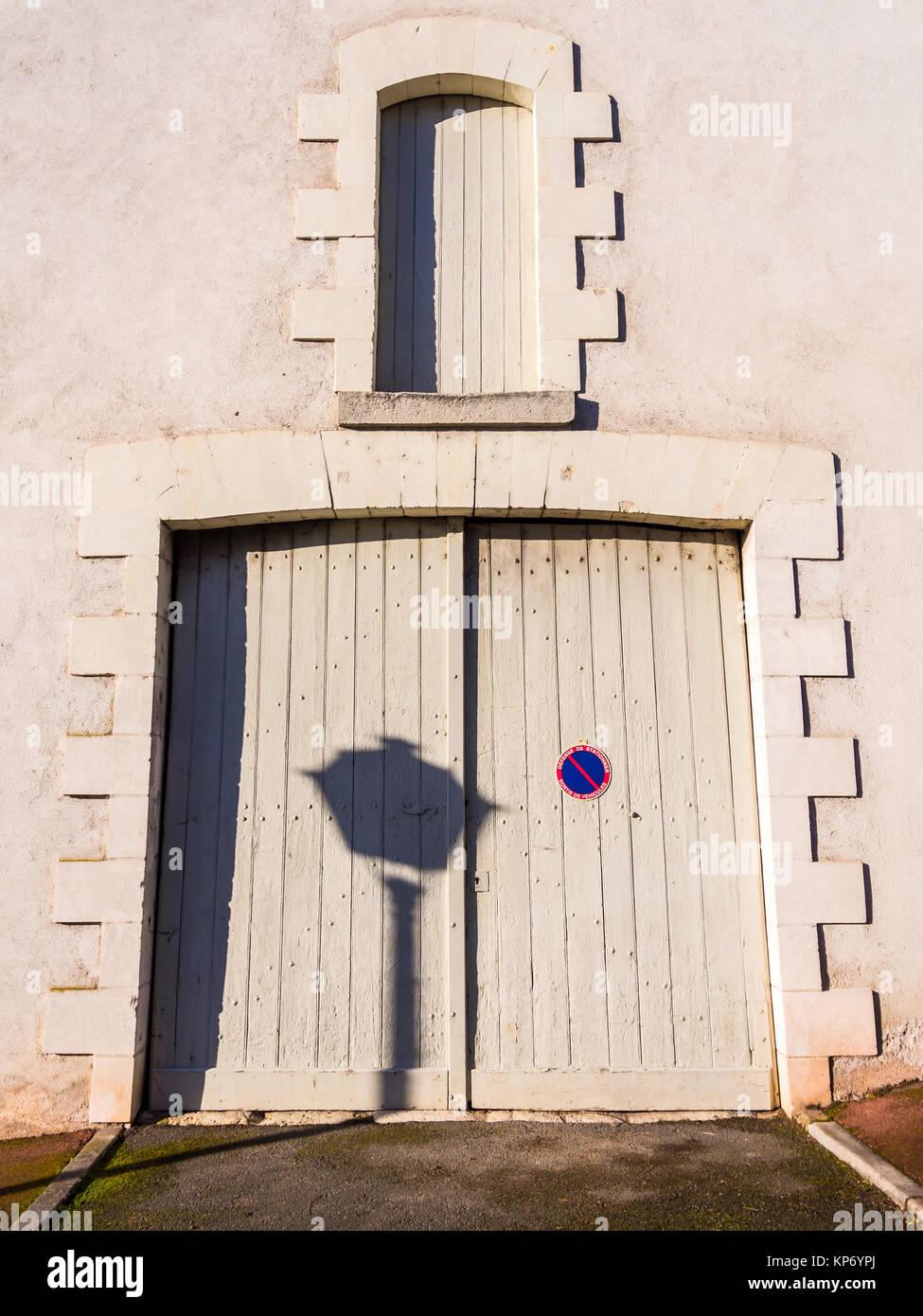 Shadow of street lamp on garage doors - France. - Stock Image