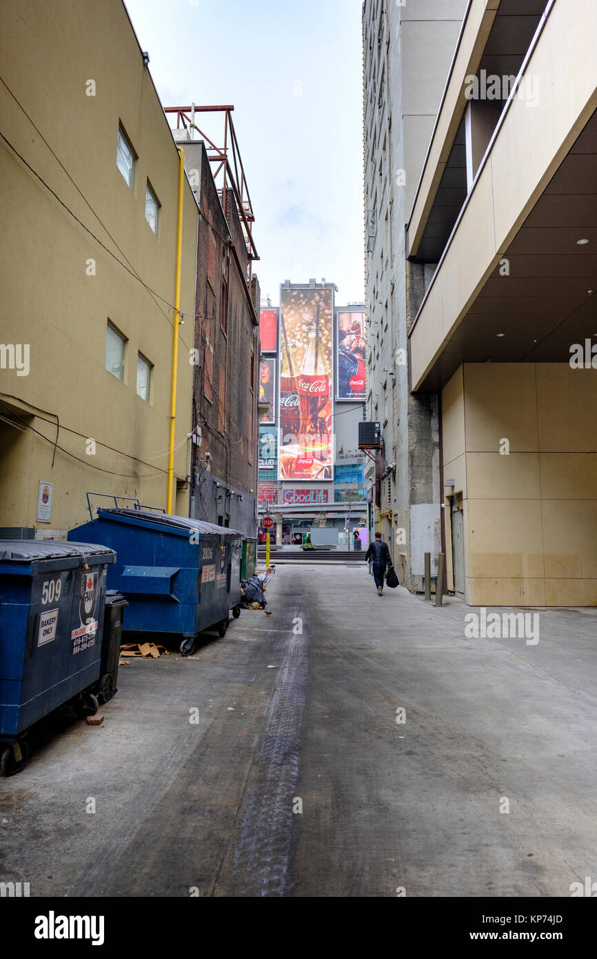 O'Keefe Lane alley close to Dundas Square, garbage dumpsters lined up against the wall, man walking, Coca-Cola - Stock Image