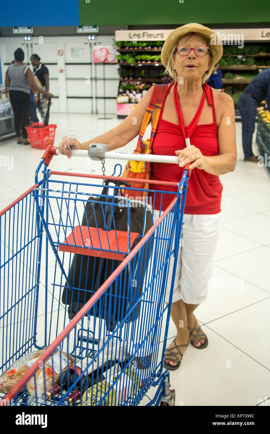 Caucasian woman pushing the grocery cart and buying grocery. She is choosing her food carefully! - Stock Image