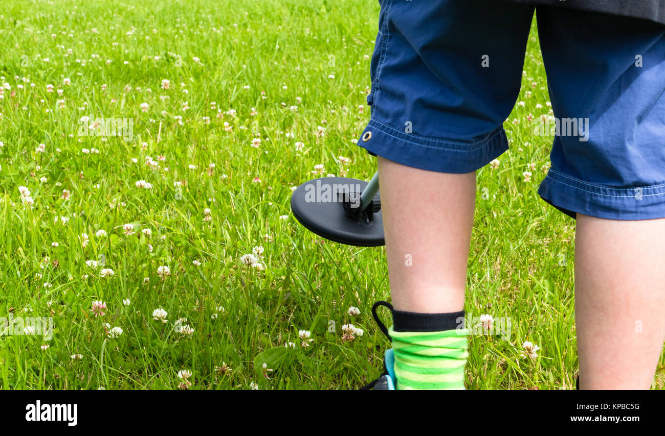 Boy searching a grass lawn with a metal detector - Stock Image