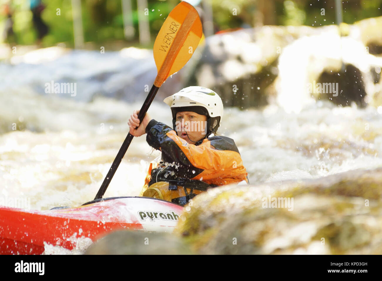 Female kayaker shooting the rapids at the National White Water Centre on the River Tryweryn in Snowdonia National Stock Photo