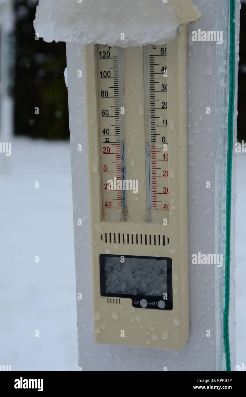 Snowy outdoor thermometer in wintry garden - Stock Image