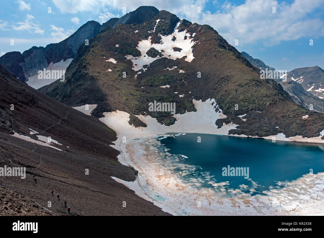 Trekkers at Tebarray mountain lake.Pyrenees.Piedrafita.Aragón.Spain - Stock Image