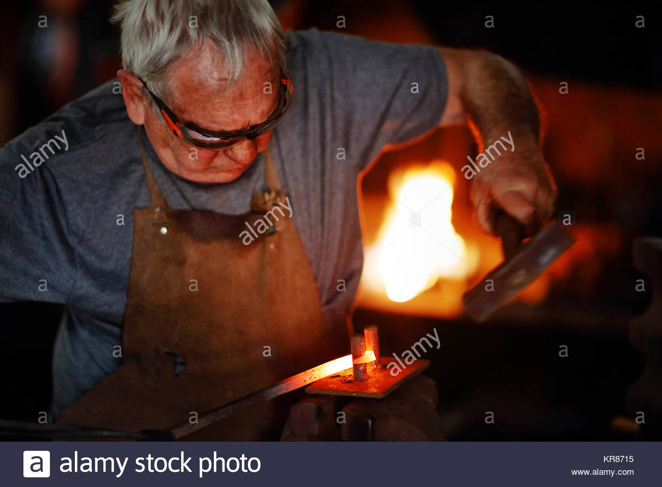 Authentic Old-Fashioned Blacksmith bending and forming red hot molten iron with hammer  in his old workshop (shallow - Stock Image