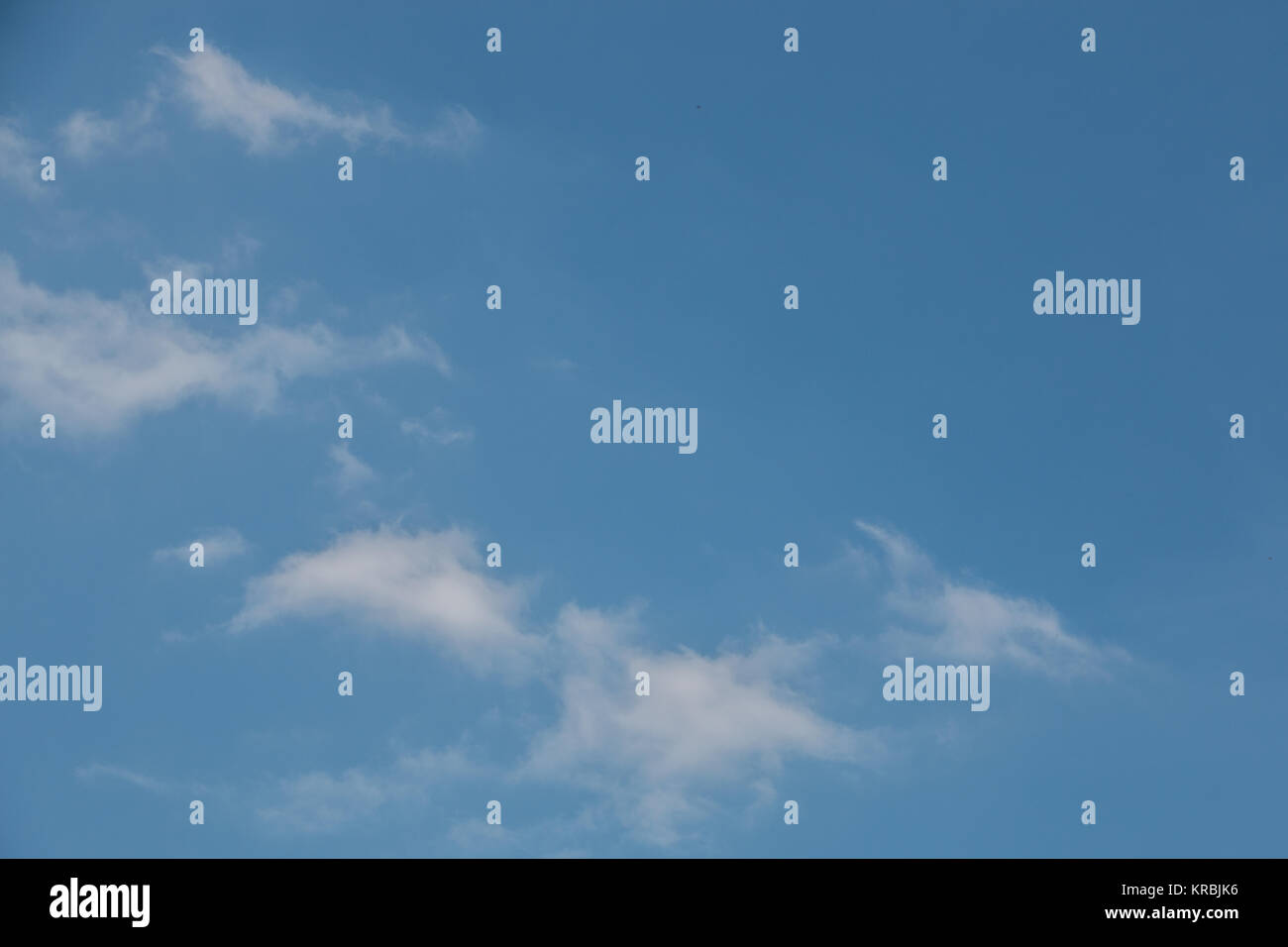 White clouds that look like a dragon or dinosaur in the deep blue sky - Stock Image