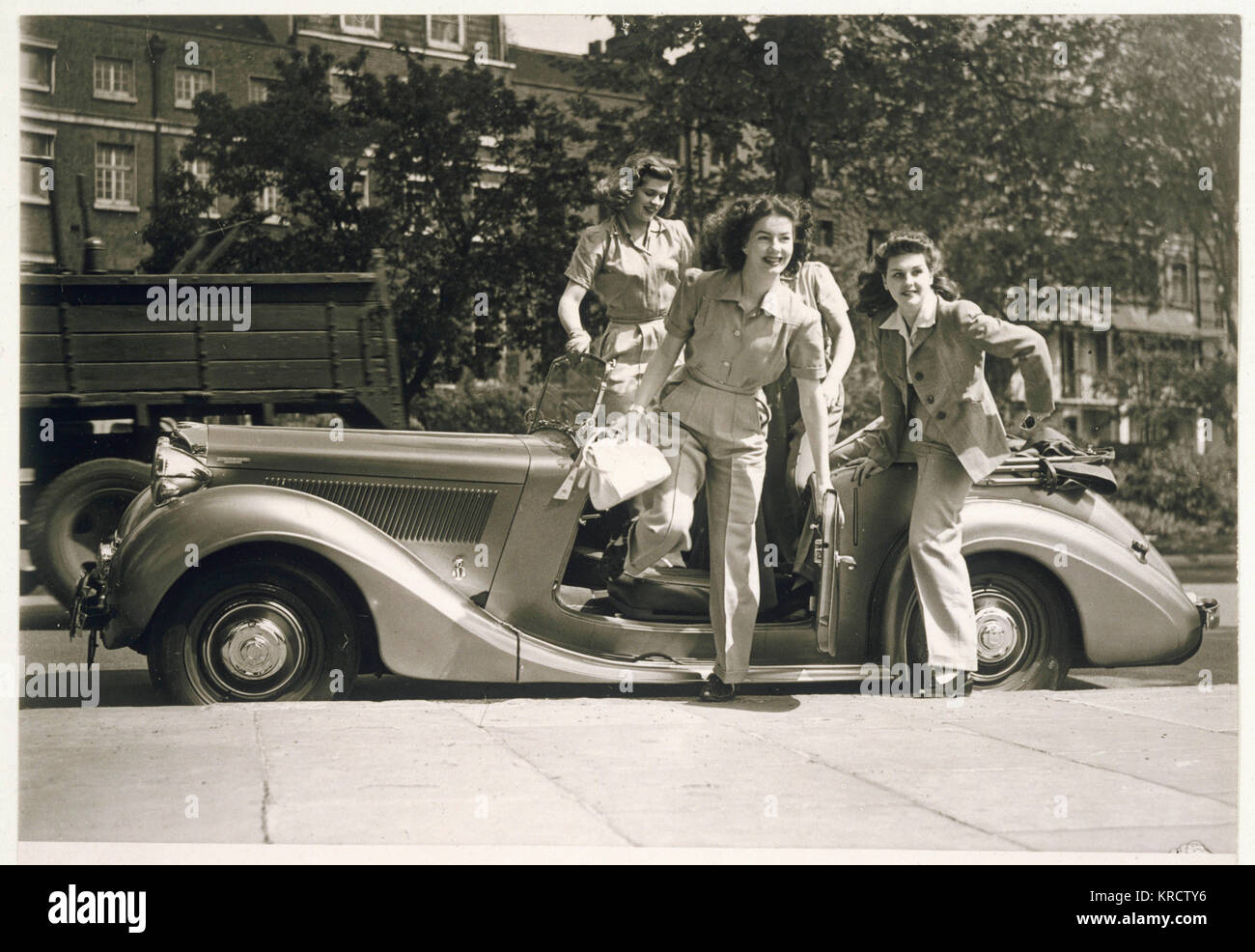 Four glamorous war-time women wearing trouser suits leap from an open top car Date: early 1940s Stock Photo
