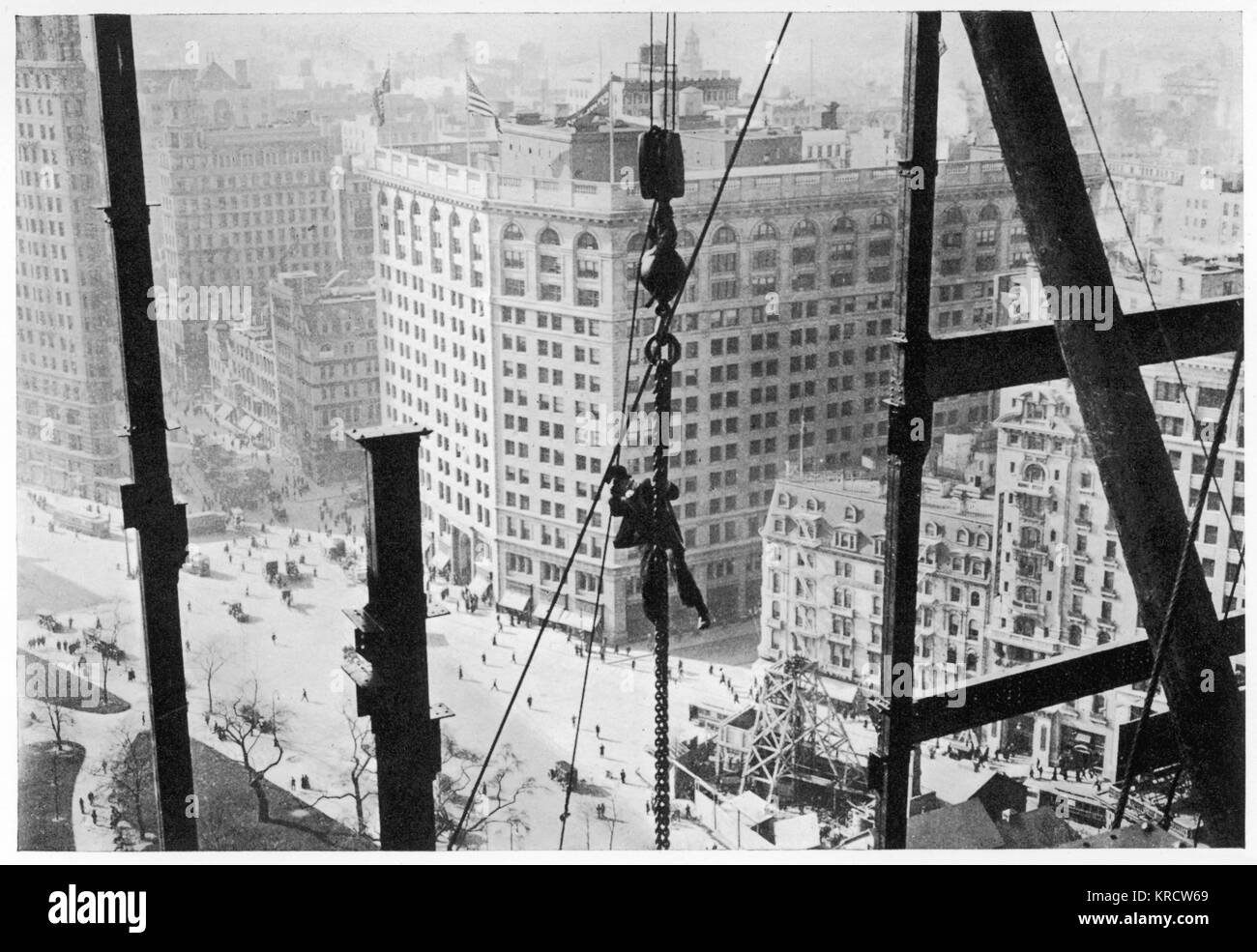A man hangs precariously from a line during the construction of a skyscraper in New York. Date: Circa 1900 - Stock Image