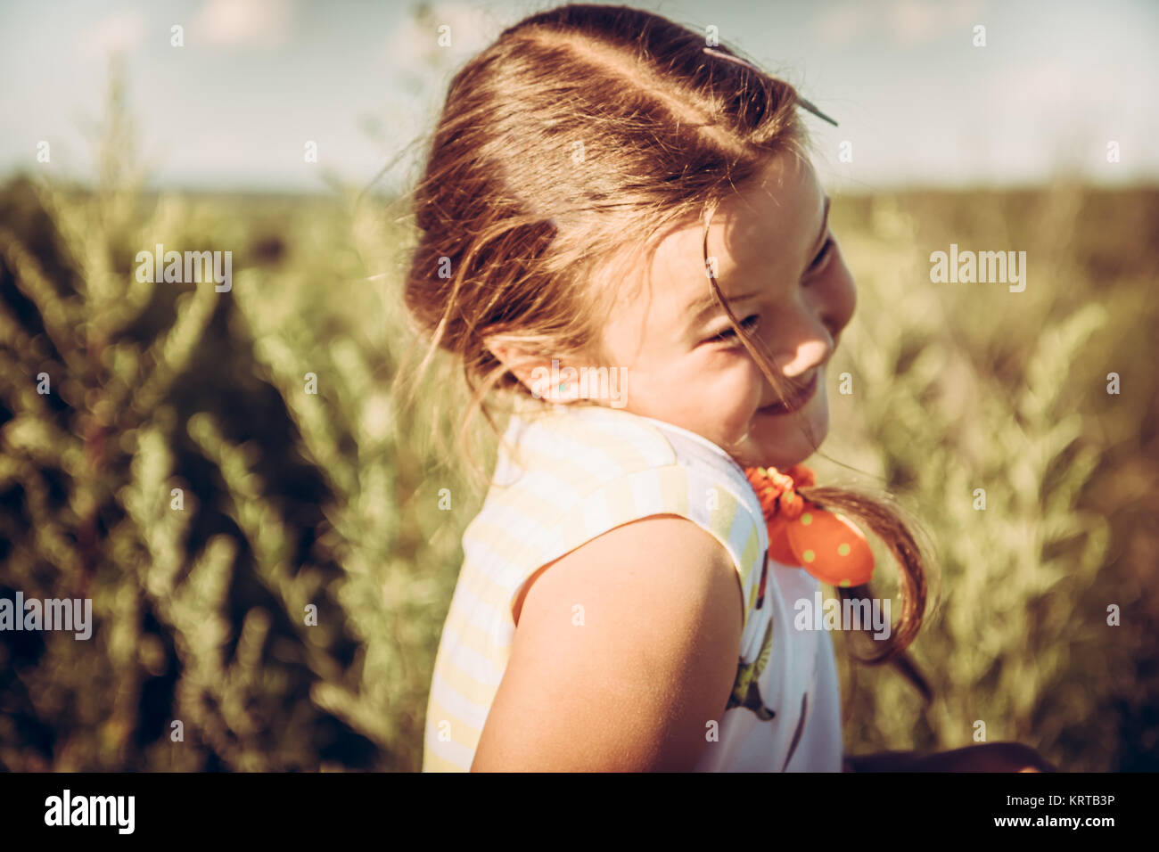 Cute shy plumpy girl in summer rural field in countryside during summer holidays symbolizing happy carefree childhood - Stock Image