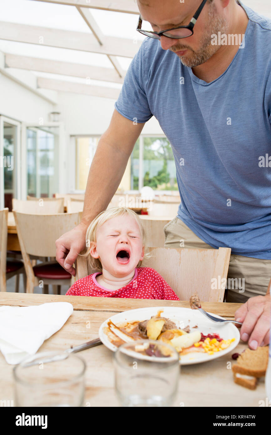 A young girl crying at the dinner table - Stock Image