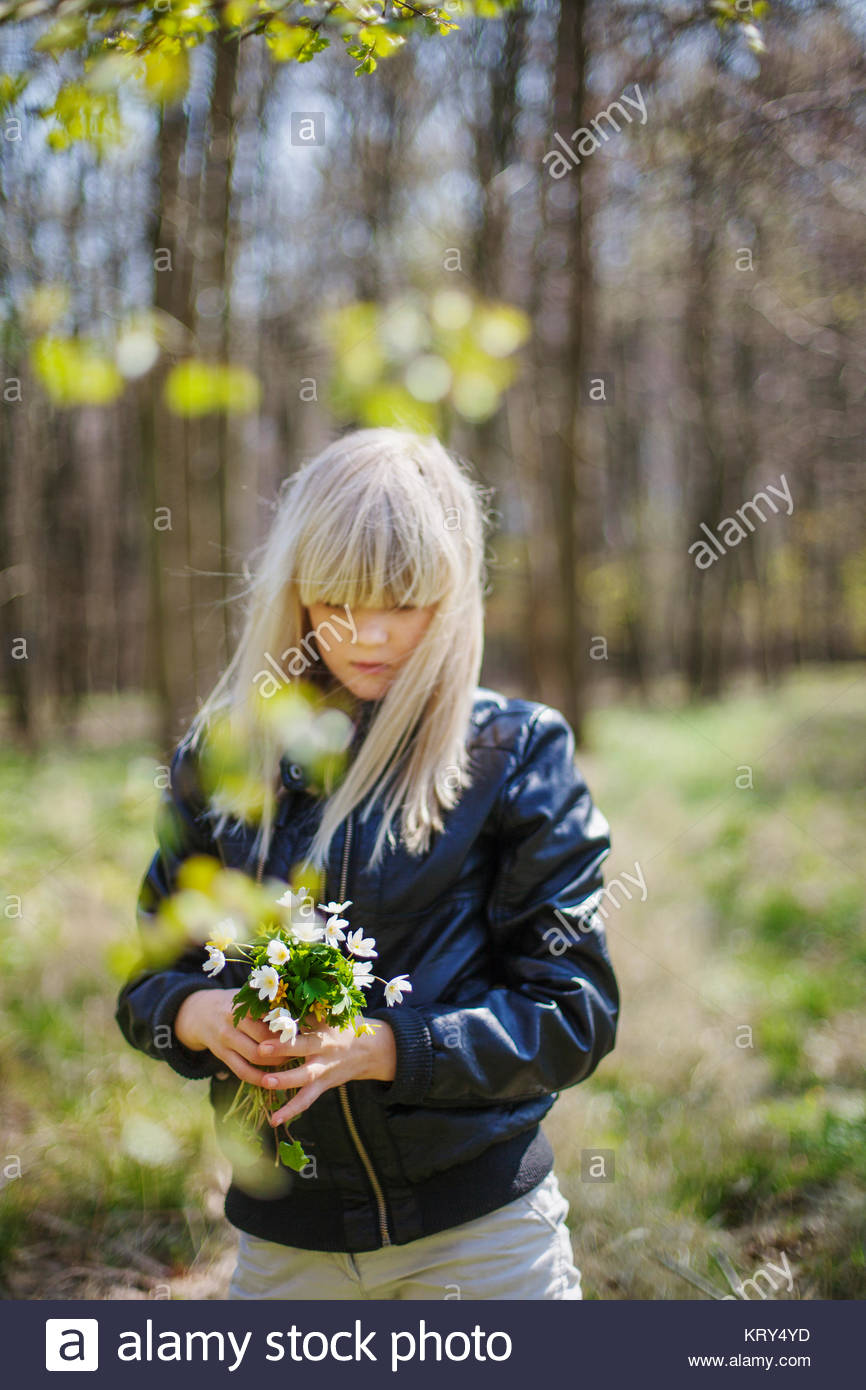 Girl gathering flowers at a forest - Stock Image