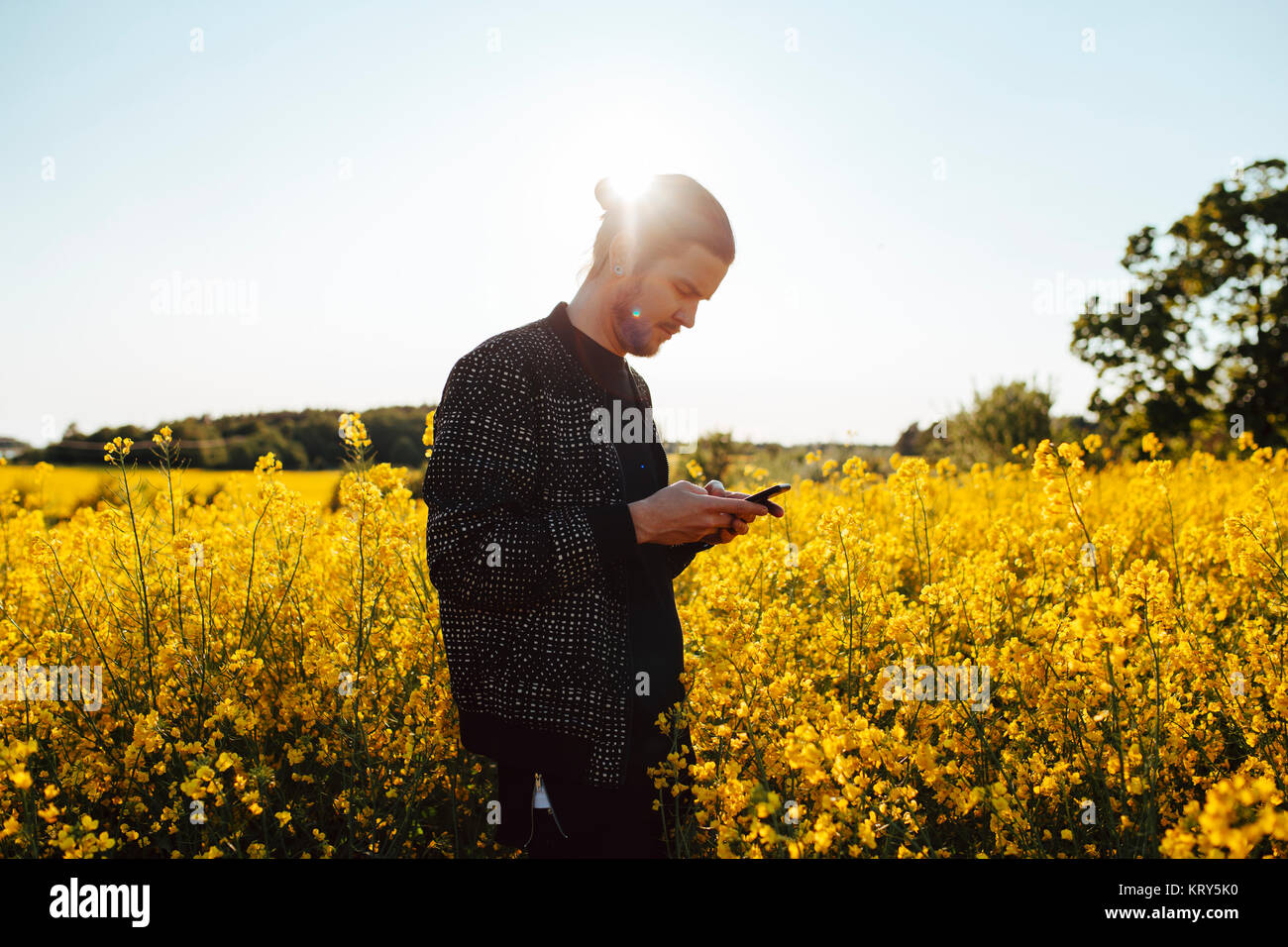 A young man outdoors looking at his cell phone - Stock Image