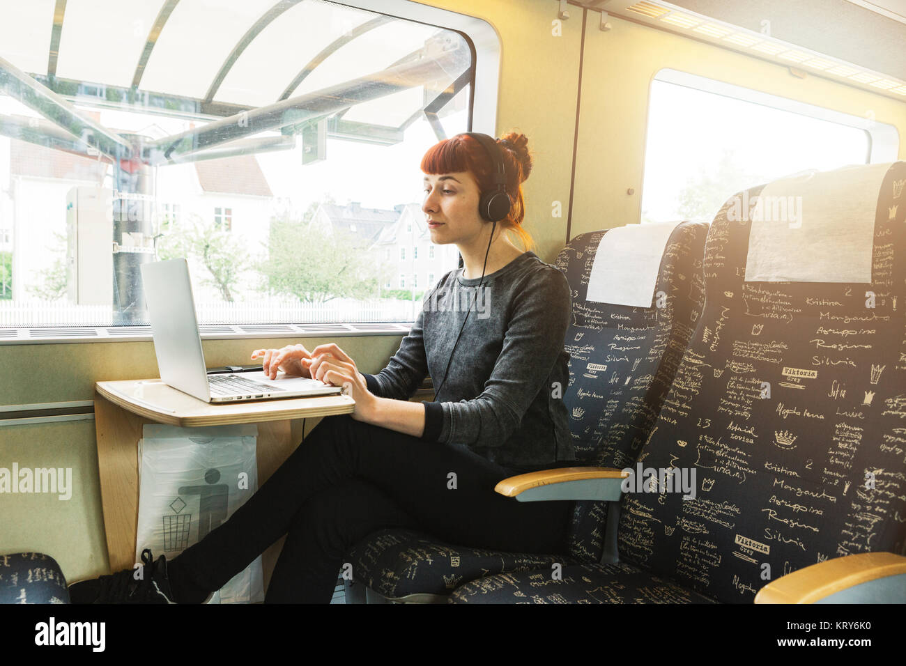 Woman using laptop on train - Stock Image