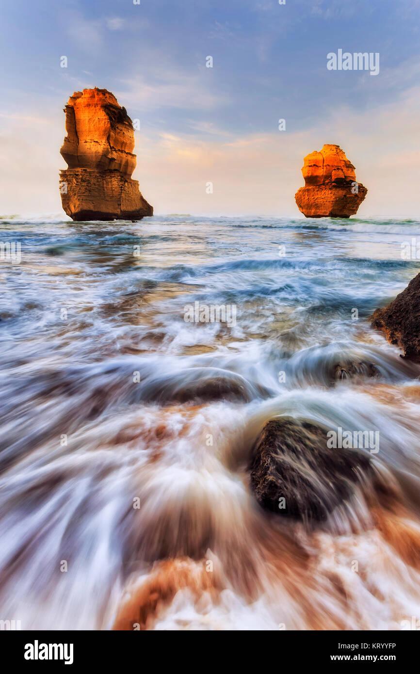 Two limestone eroded disconnected apostle rocks off Gibson Steps sandy beach on Twelve Apostles marine park at sunrise. - Stock Image