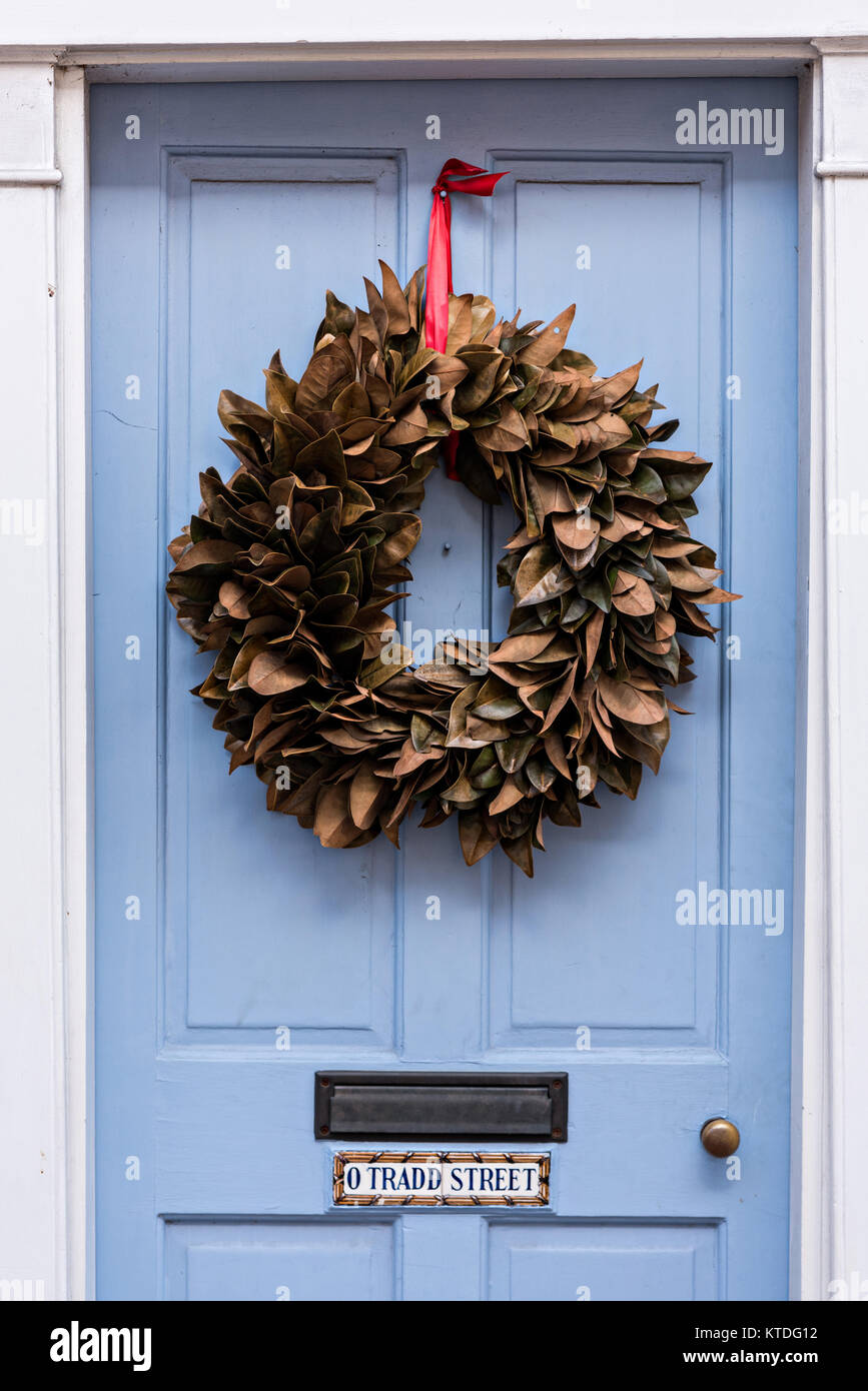 A Blue Wooden Door Of A Historic Home Decorated With A Magnolia Leaf