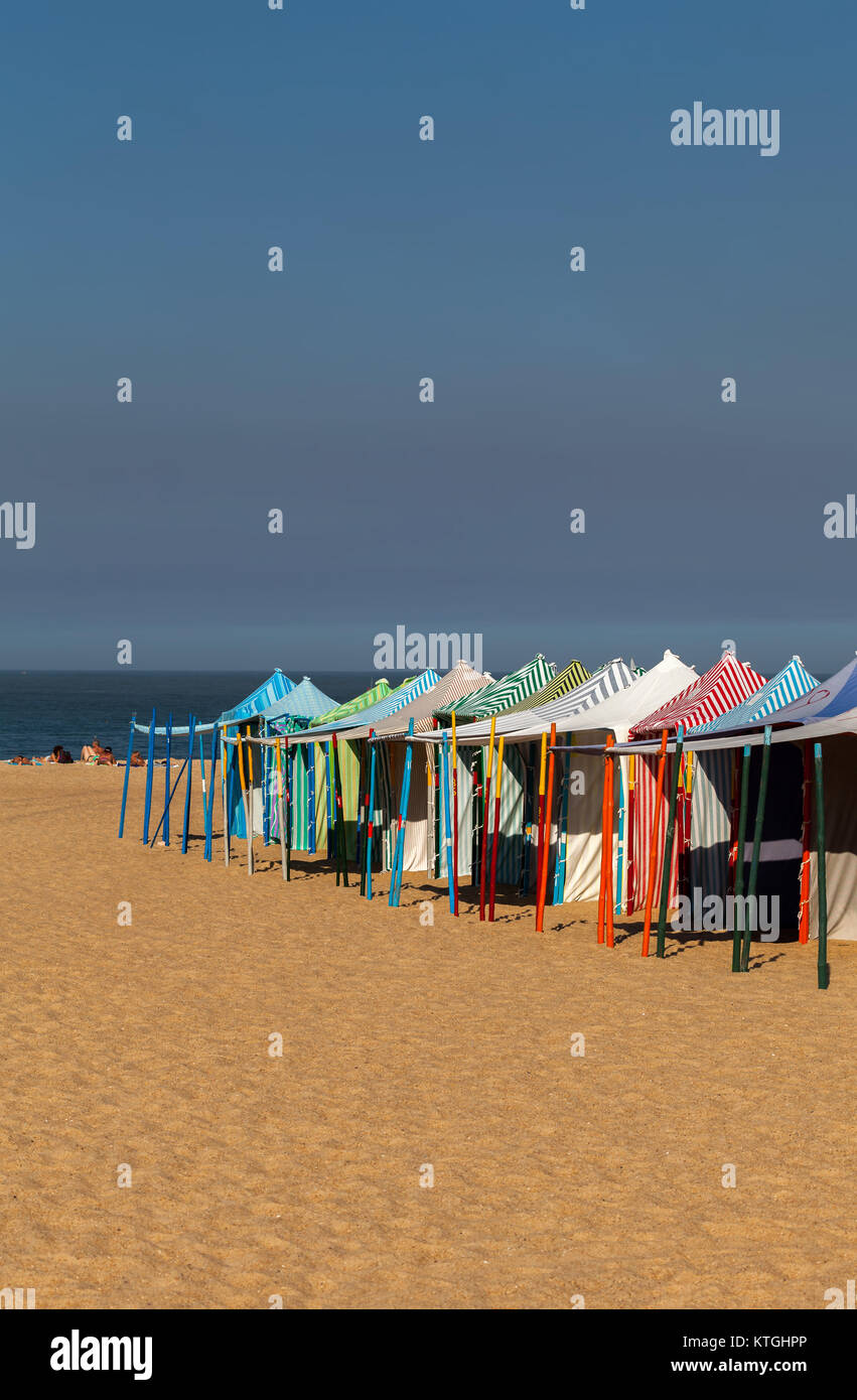Praia da Nazare beach in Nazare, Portugal, covered with the summertime beach tents. - Stock Image