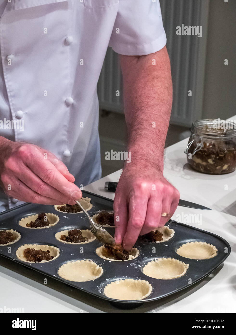 older-man-in-chef-whites-filling-mince-p