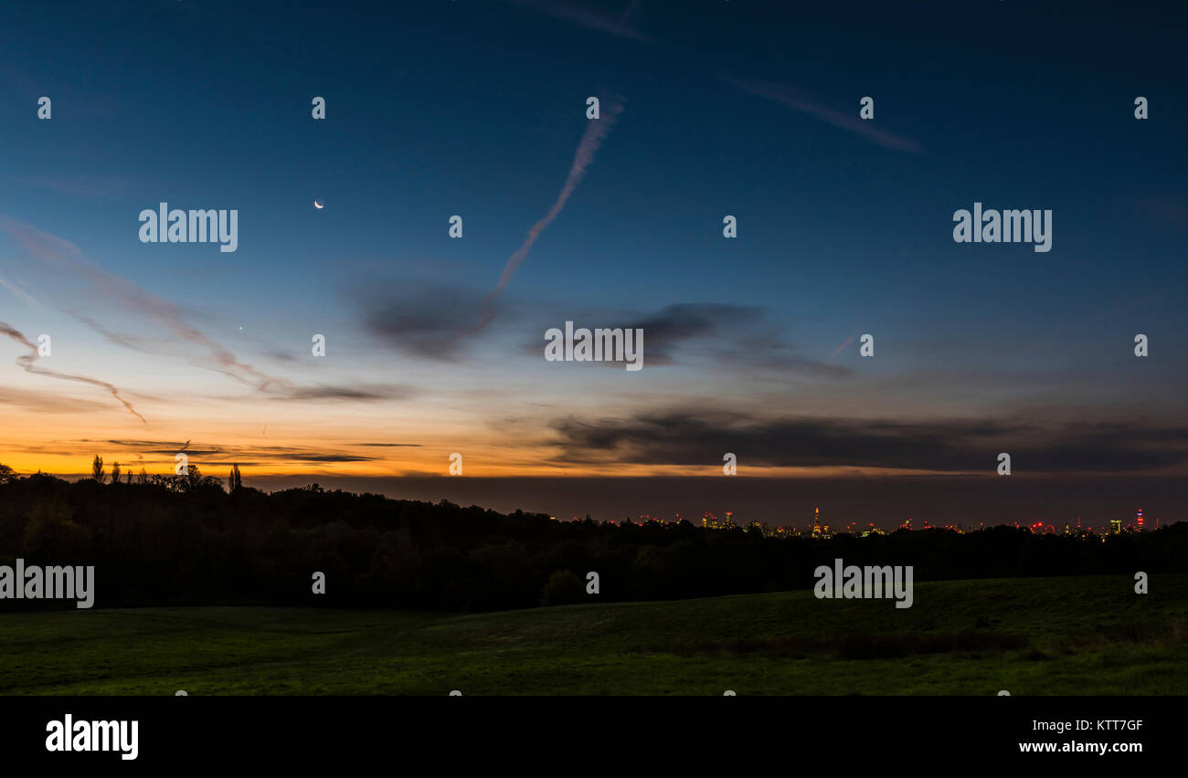 Early dawn and the moon over the London skyline from Hampstead Heath, London, UK - Stock Image