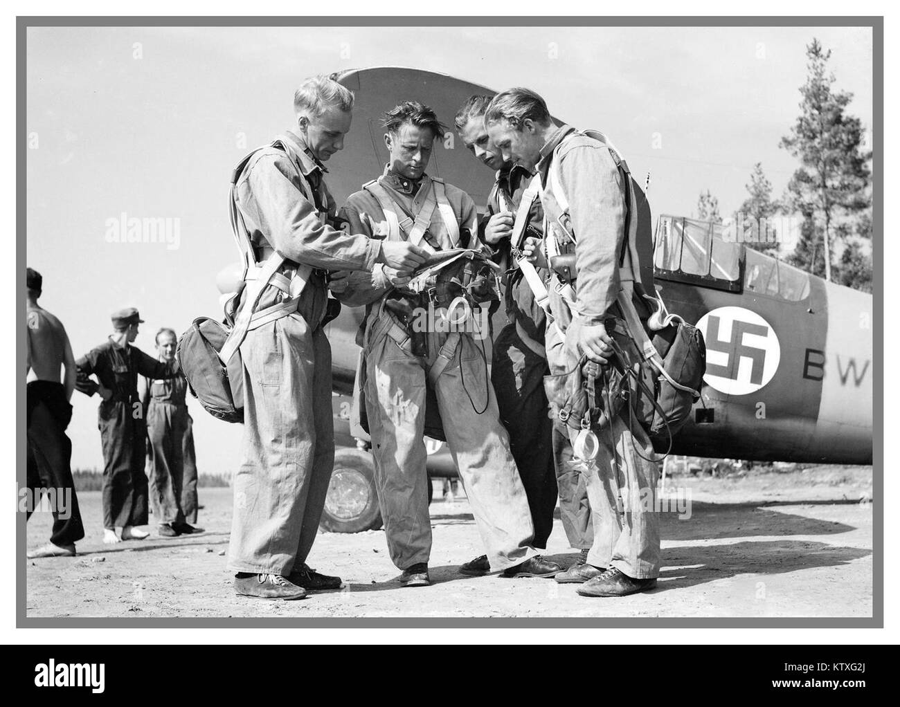 Finnish Airforce pilots during Winter War with American Brewster F2A Fighter planes behind with Swastika emblem - Stock Image