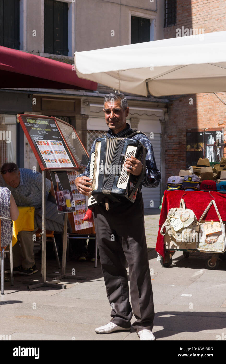 an-accordionist-playing-for-diners-in-a-small-square-in-the-san-marco-KW13RG.jpg