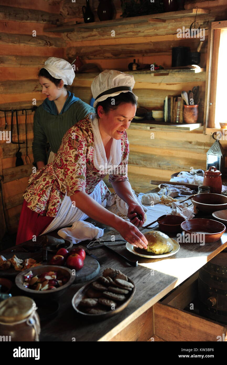 USA Virginia VA Colonial Yorktown two historical interpreters preparing a Figgy Pudding for winter holiday meal Stock Photo