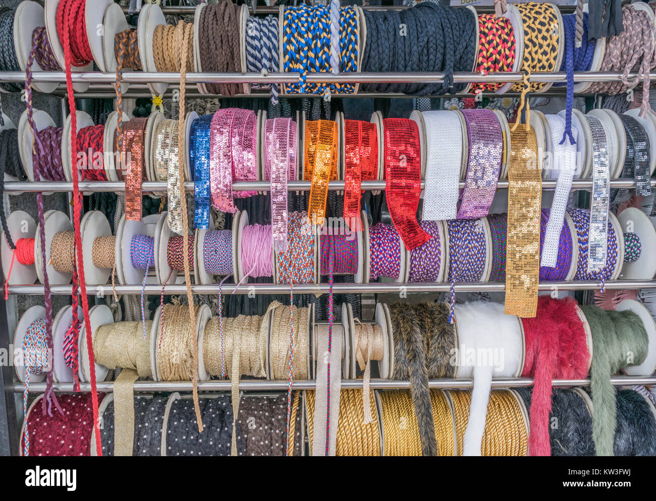 Isolated shot of sequin ribbons, colorful rope and other bric-a-brac, on a display rack - Stock Image