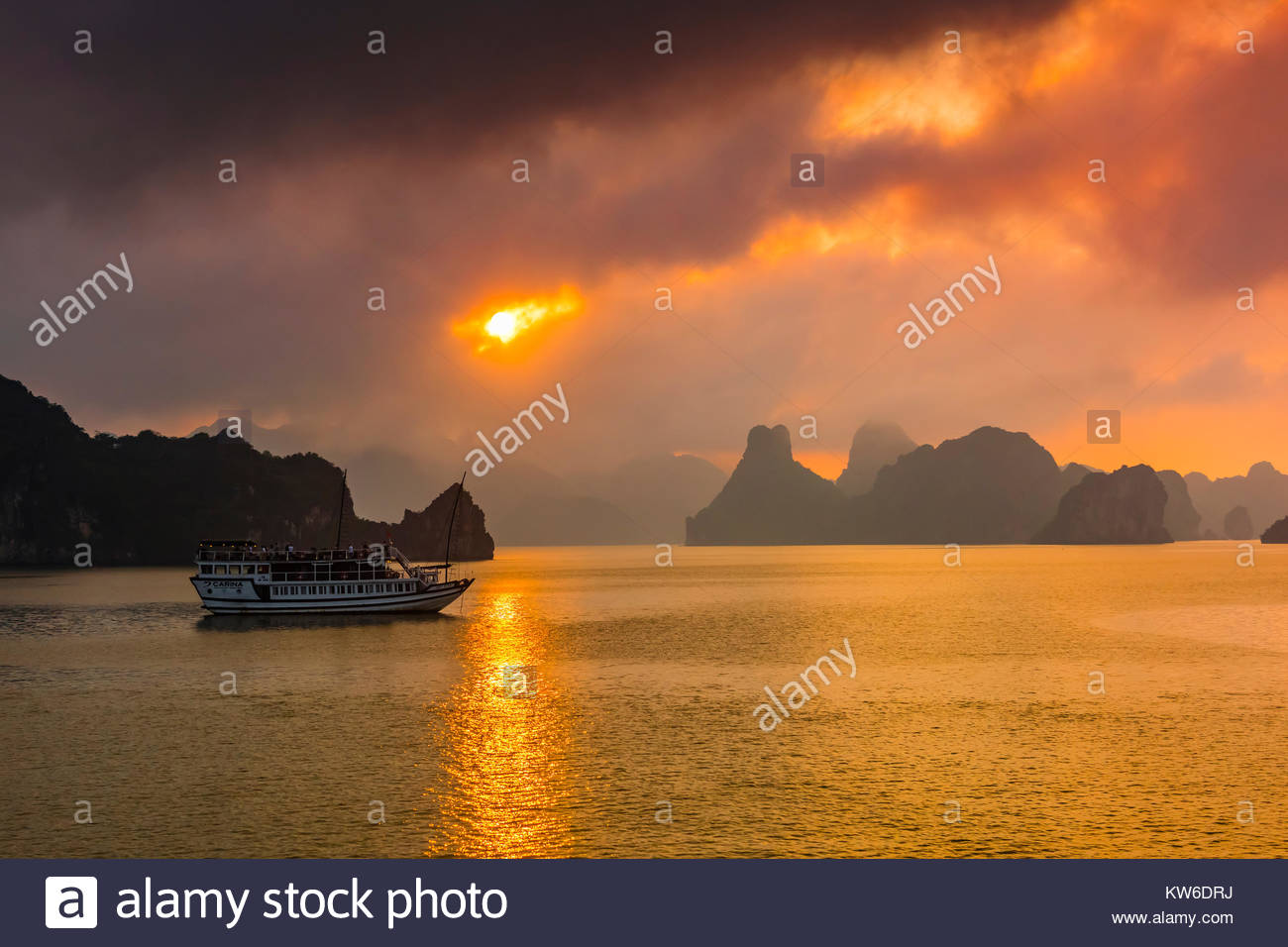 Sunset at Halong Bay, North Vietnam. The bay features 3,000  limestone and dolomite karsts and islets in various - Stock Image