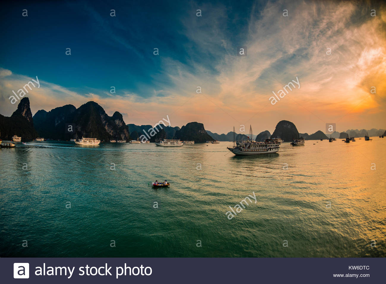 Sunset in Halong Bay, North Vietnam. The bay features 3,000  limestone and dolomite karsts and islets in various - Stock Image