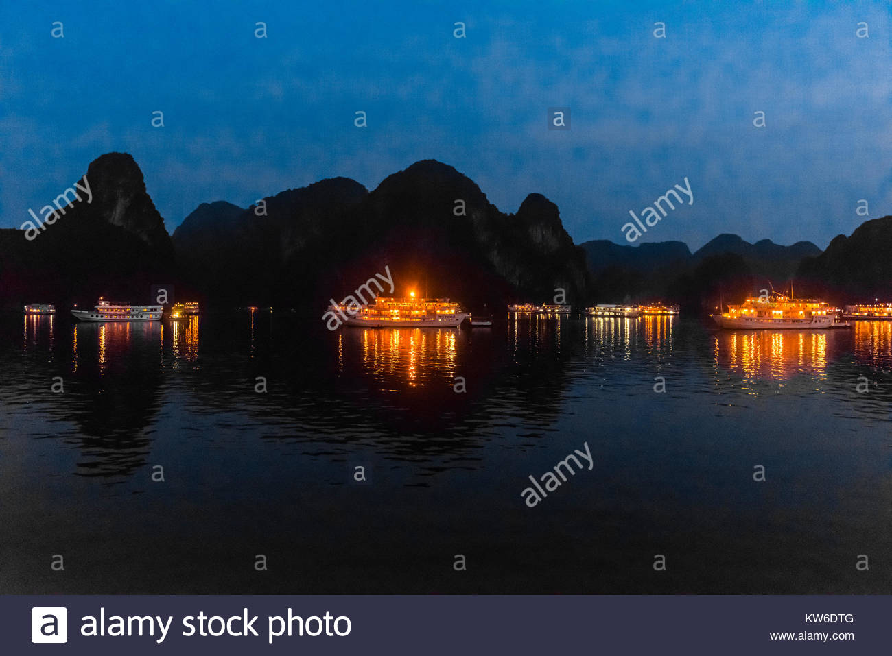 Tour ships docked for the night in Halong Bay, North Vietnam. The bay features 3,000  limestone and dolomite karsts - Stock Image