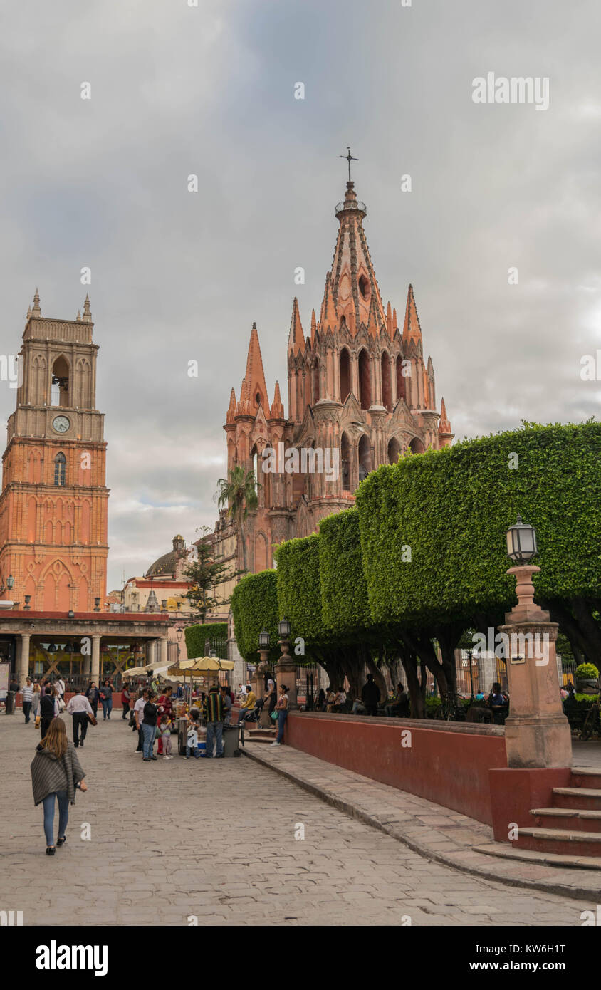 The beautiful pink Gothic Parroquia de San Miguel Arcangel towering above the El Jardin, with tourists and vendors, - Stock Image