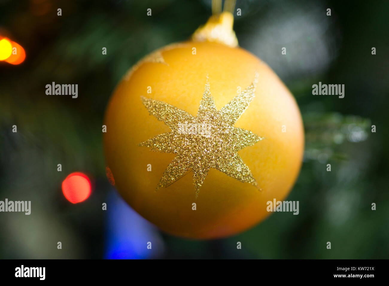 A yellow bauble with a glitter star on a Christmas tree Stock Photo