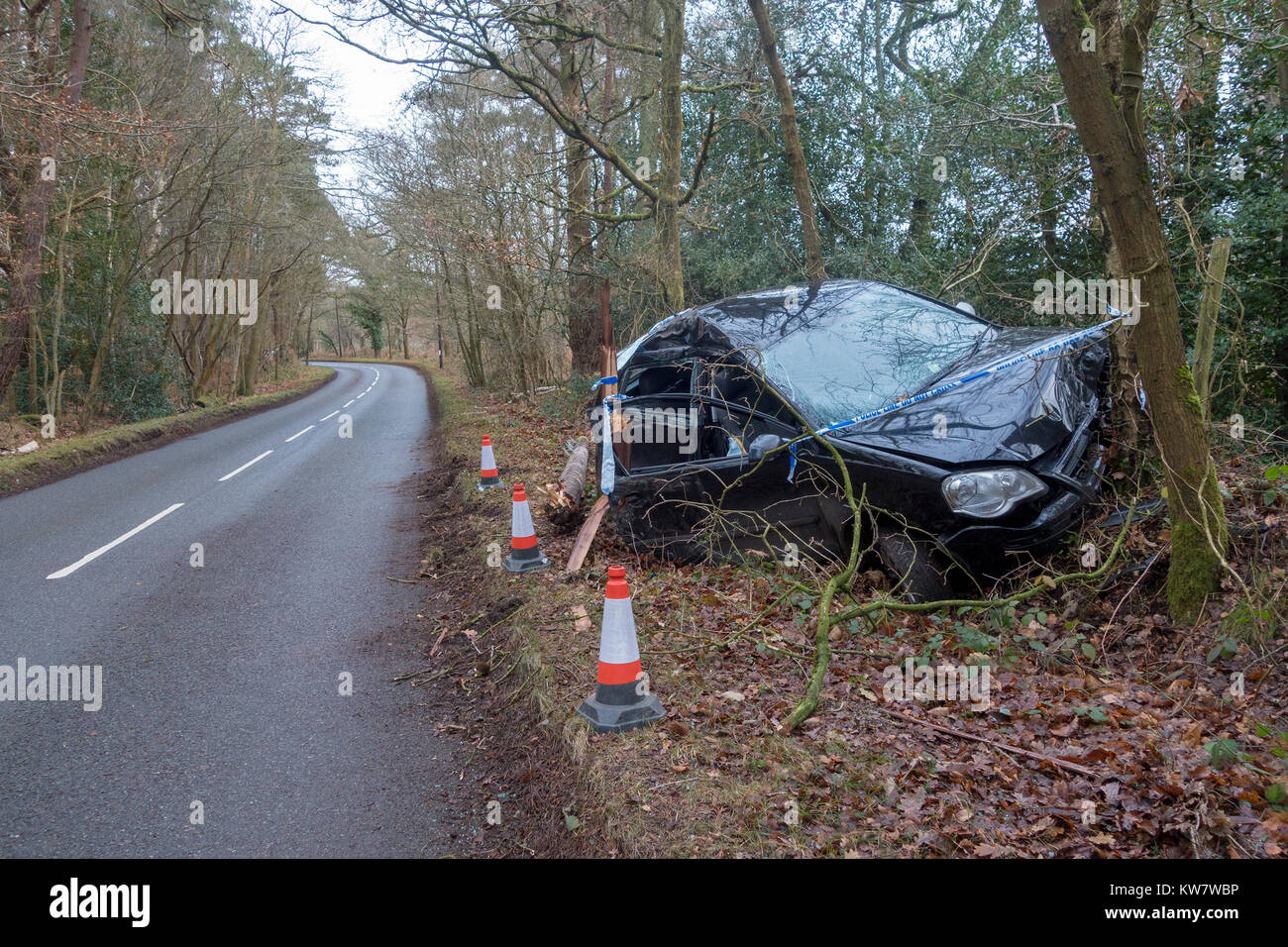 A crashed car, a black Volkswagen Polo, in a country lane surrounded by Police tape having left the road and hit - Stock Image