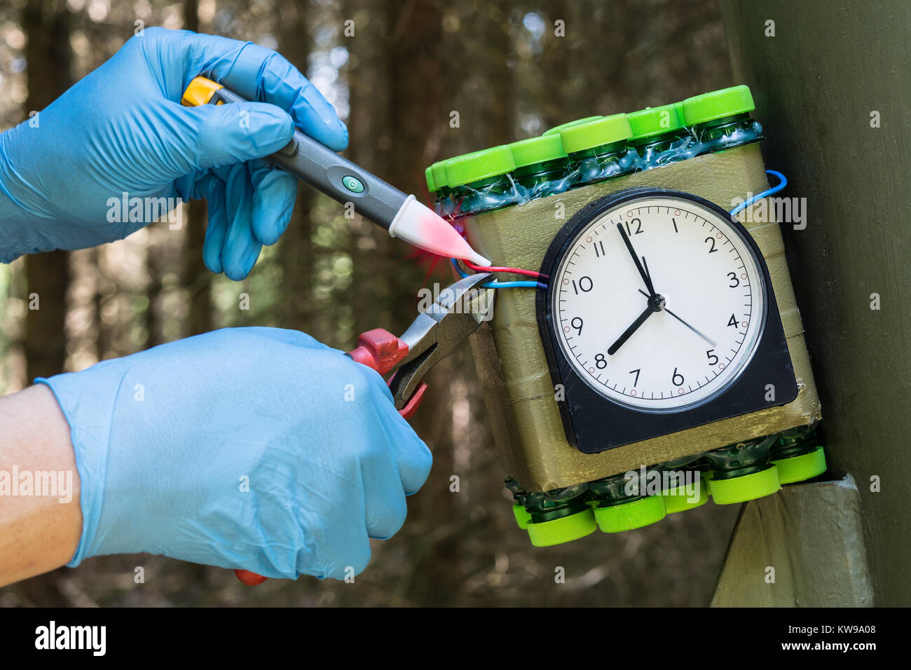 Deactivation found explosive. Imitation of timed bomb. The expert carefully disables the dangerous timebomb. - Stock Image
